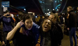 Protestors run out from the crowd after being tear gassed by Seattle police at the Interstate-5 entrance on Cherry Street in Seattle, Monday, Nov. 24, 2014. Protestors took to the streets in response to the Ferguson grand jury decision not to indict Darren Wilson in the death of Michael Brown. (AP Photo/seattlepi.com, Anna Erickson)