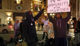 A protester holds up a placard in Beverly Hills, Los Angeles, Calf., Tuesday, Nov. 25, 2014, after the announcement of the grand jury decision not to indict Ferguson police officer Darren Wilson in the fatal shooting of Michael Brown, an unarmed 18-year-old. (AP Photo/Nick Ut)