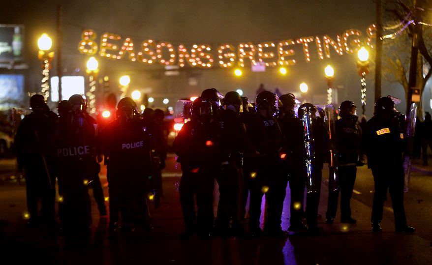 Police in riot gear use tear gas to clear the street in front of the Ferguson Police Department after the announcement of the grand jury decision not to indict police officer Darren Wilson in the fatal shooting of Michael Brown, an unarmed black 18-year-old, Monday, Nov. 24, 2014, in Ferguson, Mo. (AP Photo/Charlie Riedel)