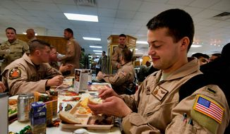1st Lt. Nick Biggs and others eating Thanksgiving dinner in Afghanistan. KBR, the company that catered the meal, said they put extra effort into providing the time-honored feast to service members. (u.s. air force)