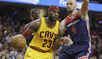 Cleveland Cavaliers' LeBron James (23) drives pat Washington Wizards' Marcin Gortat (4), from Poland, during the first quarter of an NBA basketball game Wednesday, Nov. 26, 2014, in Cleveland. (Associated Press)