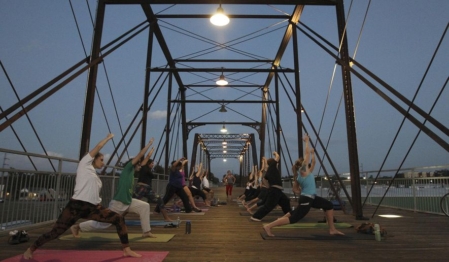 "ADVANCE FOR USE MONDAY, DEC. 1 AND THEREAFTER - In this photo taken on Oct. 10, 2014, participants stretch during a yoga class, led by Mobile Om founder Cassandra Fauss, on the Hays Street Bridge in San Antonio. ""We believe that the most sacred space for yoga is not found inside any studio, temple or ashram, but instead, it is the space that is created within,"" Fauss said. She teaches yoga twice a week on the bridge. (AP Photo/The San Antonio Express-News, Kin Man Hui)  RUMBO DE SAN ANTONIO OUT; NO SALES"