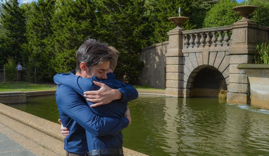 ADVANCE FOR USE SUNDAY, NOV. 30, 2014, AND THEREAFTER- In this Oct. 18, 2014, photo provided by Michael Knaapen, Andrew Nasonov hugs Igor Bazilevsky, left, after the couple was married at Meridian Hill Park in Washington. They both came to the U.S. from Russia in July, and are preparing to file an application seeking asylum in the U.S. The increase in the overall applications for asylum by Russians is due in part to the worsening anti-gay climate in Russia, according to Immigration Equality, a New York-based organization which provides legal services for lesbian, gay, bisexual and transgender immigrants. (AP Photo/Michael Knaapen)