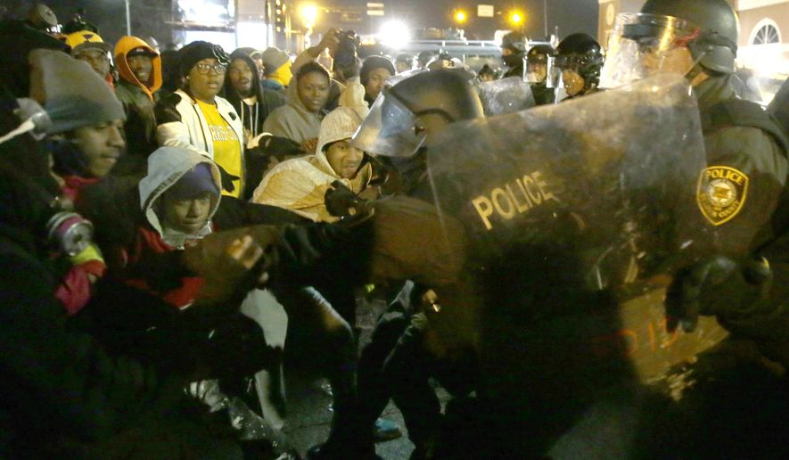 Police officers confront protesters Tuesday, Nov. 26, 2014, in Ferguson, Mo. Missouri's governor ordered hundreds more state militia into Ferguson on Tuesday, after a night of protests and rioting over a grand jury's decision not to indict police officer Darren Wilson in the fatal shooting of Michael Brown, a case that has inflamed racial tensions in the U.S. (AP Photo/David Goldman)