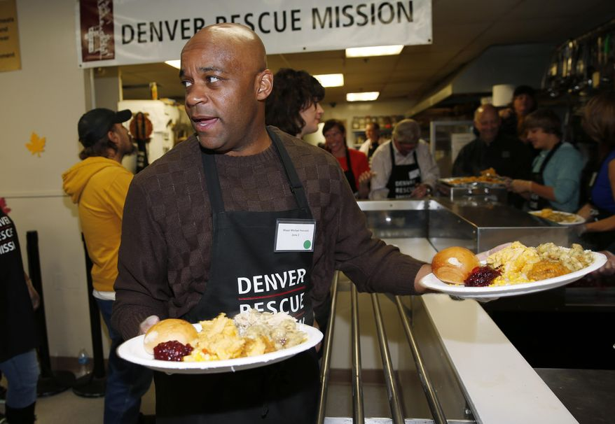 Denver Mayor Michael Hancock carries plates to serve traditional Thanksgiving Day dinners to more than 500 homeless and poor men, women and children at the Denver Rescue Mission in downtown Denver on Wednesday, Nov. 26, 2014. (AP Photo/David Zalubowski) ** FILE **