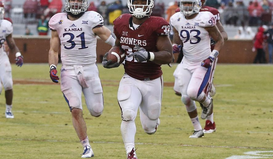 FILE - In this Nov. 22, 2014, file photo, Oklahoma's Samaje Perine (32) sprints towards the end zone on a touchdown run ahead of Kansas's Ben Heeney (31) and Kansas's Ben Goodman (93) in the second quarter of an NCAA college football game in Norman, Okla. College football teams have been running wild this season, averaging more yards per carry and per game than at any time in recent years.  (AP Photo/Sue Ogrocki, File)