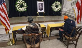 A portrait of Marion Barry is displayed at the John A. Wilson Building, which houses the offices of the mayor and city council, in Washington, Wednesday, Nov. 26, 2014, as Kim Harrison, left, signs a condolence book and pays her respects to Barry, who served four terms as mayor and another 16 years on the D.C. Council. Barry died Sunday morning at age 78. (AP Photo/J. Scott Applewhite)