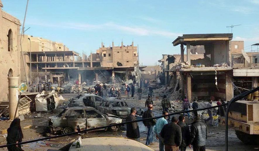 This photo provided on Tuesday, Nov. 25, 2014, by an anti-Islamic State group and anti-Bashar Assad activist group Raqqa Is Being Slaughtered Silently, which has been authenticated based on its contents and other AP reporting, showa burned cars and damaged buildings on a street after Syrian government forces airstrikes struck a popular market near a museum and an industrial neighborhood in Raqqa city, north Syria. The death toll from a series of Syrian government airstrikes on the Islamic State group's stronghold in northeastern Syria has risen to at least 95, making it one of the deadliest attacks on the city of Raqqa in the past three years. (AP Photo/Raqqa Is Being Slaughtered Silently)
