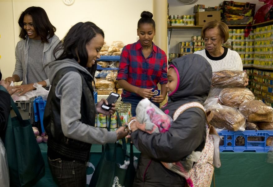 From left, First lady Michelle Obama, Sasha Obama, and the first lady's mother, Marian Robinson, distribute food at Bread for the City Wednesday, Nov. 26, 2014, in Washington, as part of an annual Thanksgiving tradition of participation in a service event.  (AP Photo/Jacquelyn Martin)