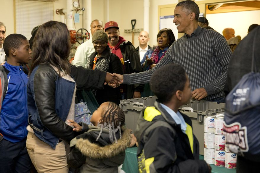 "President Barack Obama shakes hands with a parton as he and his family distribute food at ""Bread For The City"" Wednesday, Nov. 26, 2014, in Washington, as part of an annual Thanksgiving tradition of participation in a service event.  (AP Photo/Jacquelyn Martin)"