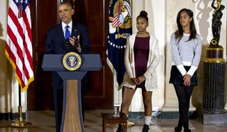 President Barack Obama, joined by his daughters Malia, right, and Sasha, center, speaks at the White House, in Washington, Wednesday, Nov. 26, 2014, during the presidential turkey pardon ceremony, an annual Thanksgiving tradition. (AP Photo/Jacquelyn Martin)