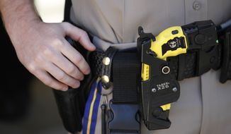 A Taser X26 stun gun is seen on a California Highway Patrol's belt. A 2011 Justice Department study on the use of Tasers and other nonlethal weapons concluded they can spare lives and injury for both suspects and officers. (Associated Press) **FILE**