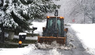 A heavy wet snow covers pine trees as public works director Shannon Clem plows snow along 7th Street in Grottoes, Va., Wednesday, Nov. 26, 2014. (AP Photo/The Daily News-Record, Michael Reilly)  ** FILE **