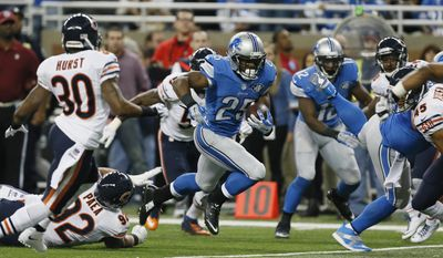 Detroit Lions running back Theo Riddick (25) runs through the Chicago Bears defense during the first half of an NFL football game in Detroit, Thursday, Nov. 27, 2014. (AP Photo/Paul Sancya)
