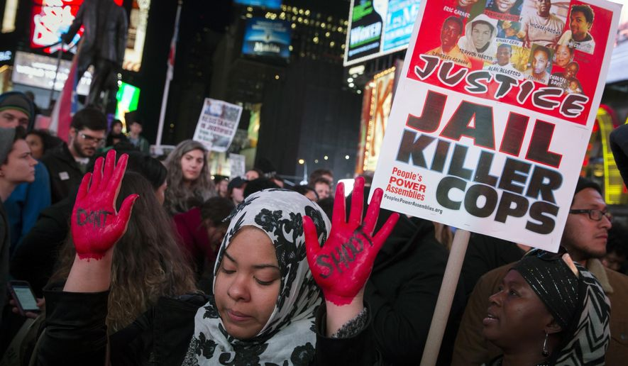 In this Nov. 25, 2014, file photo, demonstrator Maryam Said in New York raises her painted hands during a protest against a grand jury's decision on Monday not to indict Ferguson Police Officer Darren Wilson in the shooting of Michael Brown. (AP Photo/John Minchillo, File)