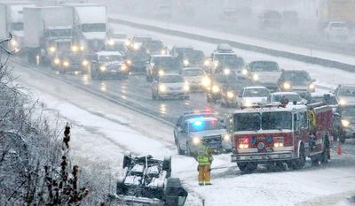 A over-turned automobile on Interstate 84 snarls traffic, Wednesday, Nov. 26, 2014 in Vernon, Conn.  The National Weather Service has issued a winter storm warning, calling for snow during the day on Wednesday, changing to rain and snow in the evening with rain and snow showers possible on Thanksgiving day. (AP Photo/Journal Inquirer, Jared Ramsdell)  MANDATORY CREDIT