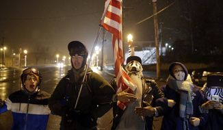 A group of protesters stand near the Ferguson Police Department on Wednesday, Nov. 26, 2014, in Ferguson, Mo. A grand jury's decision not to indict a Ferguson police officer, Darren Wilson, in the shooting death of Michael Brown has sparked protests nationwide, triggering debates over the relations between black communities and law enforcement. (AP Photo/David Goldman)