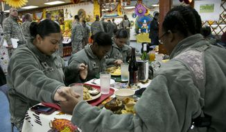 U.S. Army soldiers serving in the NATO-led peacekeeping mission in Kosovo pray before sharing a traditional Thanksgiving meal in the U.S. military base Camp Bondsteel, near the village of Sojevo in Kosovo on Thursday, Nov. 27, 2014. It is the 15th Thanksgiving for hundreds of U.S. solders serving in the NATO-led peacekeeping mission in Kosovo. (AP Photo/Visar Kryeziu)