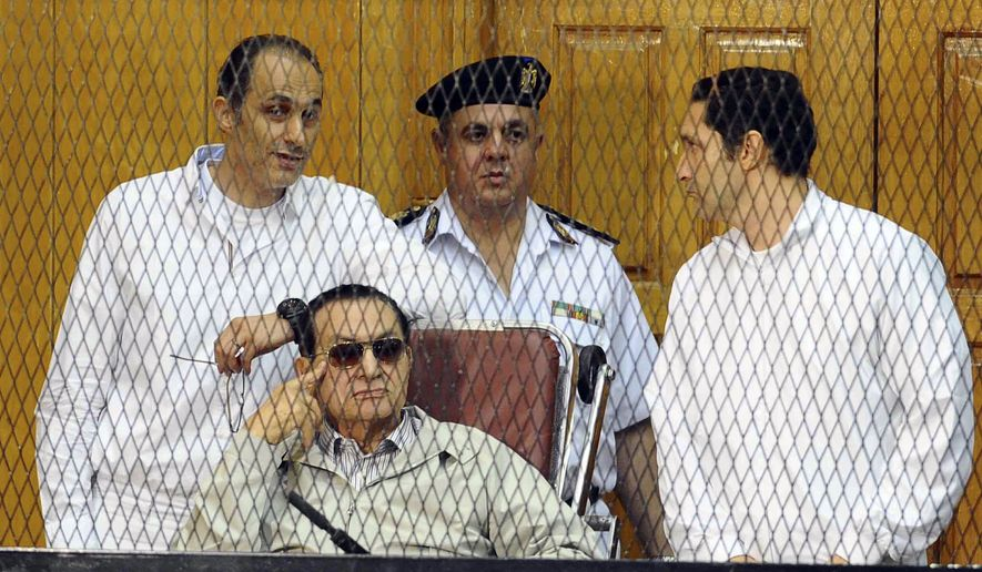 Former Egyptian President Hosni Mubarak, seated, and his two sons Gamal Mubarak, left, and Alaa Mubarak, right, attend a hearing in a courtroom at the Police Academy, Cairo, Egypt, in this Sept. 14, 2013, file photo. (AP Photo/Ahmed Omar, File)
