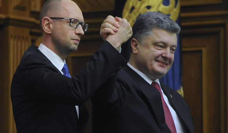 Ukraine's President Petro Poroshenko, right, celebrates with Arseniy Yatsenyuk after Yatsenyuk was appointed as Prime Minister during the opening first session of the Ukrainian parliament in Kiev, Ukraine, Thursday, Nov. 27, 2014. Parliament in Ukraine has opened for its first session since an election last month that ushered in a spate of pro-Western parties. (AP Photo/Andrew Kravchenko, Pool)