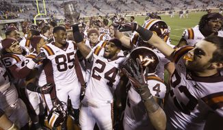 FILE - In this Nov. 30, 2013, file photo, Virginia Tech linebacker Tariq Edwards (24) holds the Commonwealth Cup as he and his teammates celebrate their 16-6 win over Virginia after an NCAA college football game in Charlottesville, Va. Virginia Tech isn't accustomed to this. The Hokies go into their annual game against Virginia needing to win to make a bowl game, and facing a team with the same intentions. (AP Photo/Steve Helber, File)