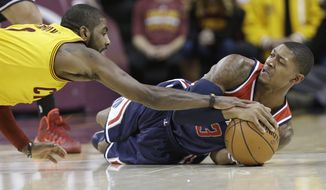Cleveland Cavaliers' Kyrie Irving, left, battles with Washington Wizards' Bradley Beal for a loose ball during the third quarter of an NBA basketball game, Wednesday, Nov. 26, 2014, in Cleveland. The Cavaliers defeated the Wizards 113-87. (AP Photo/Tony Dejak)