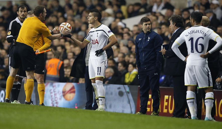 The referee Yevhen Aranovsky takes the ball from Tottenham's Erik Lamela as he halts the match after three separate pitch invasions during the Europa League group C soccer match between Tottenham Hotspur and Partizan Belgrade at White Hart Lane stadium in London, Thursday, Nov. 27, 2014 .(AP Photo/Alastair Grant)