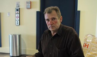 In this Sept. 12, 2014 photo, Yury Decyatnik poses for a photo as he holds his immigration paperwork in Seattle. Decyatnik has been under a final order of removal from the United States for years, but he was born in the Ukraine when it was part of the Soviet Union, so there is no country to take him back if he were to be deported. (AP Photo/Chris Grygiel)