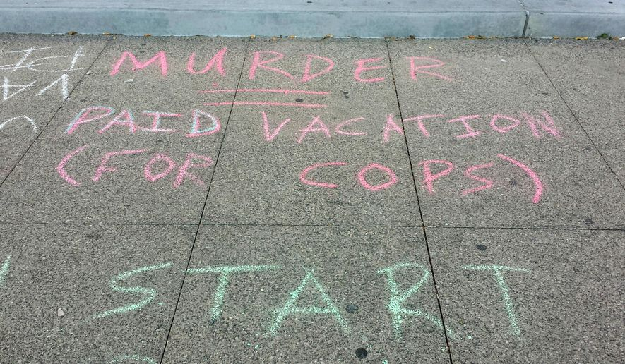 This Thursday, Nov. 27, 2014 photo shows one of many protest messages written in sidewalk chalk outside the Regional Justice Center in Las Vegas. Members of the group Sunset Activist Collective, some of whom were arrested in a similar protest last year, said they want more accountability for police involved in shootings. (AP Photo/Michelle Rindels)