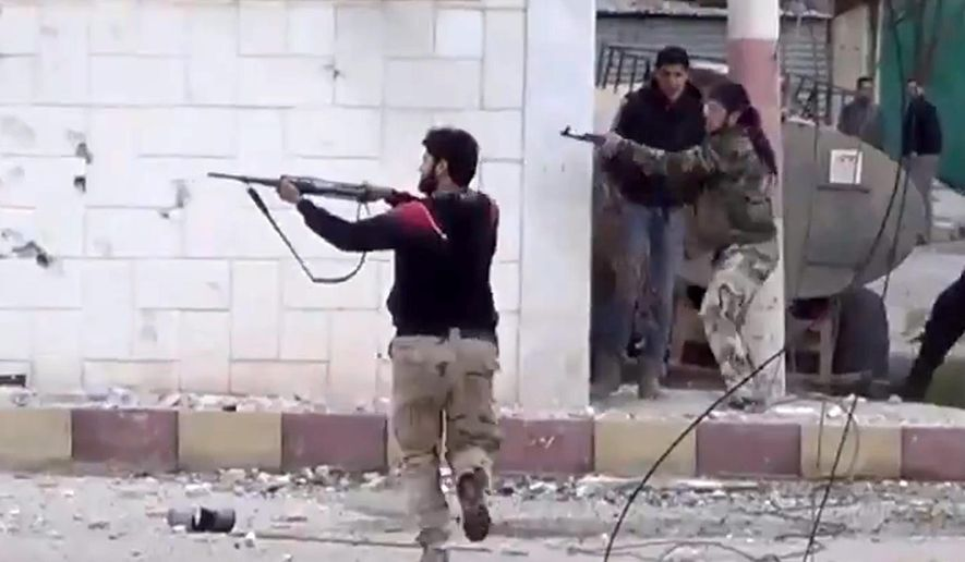 In this March 18, 2013, file image taken from video obtained from the Shaam News Network, which has been authenticated based on its contents and other AP reporting, free Syrian Army fighters fire at Syrian army soldiers during a fierce firefight in Daraa al-Balad, Syria. (AP Photo/Shaam News Network via AP video, File)