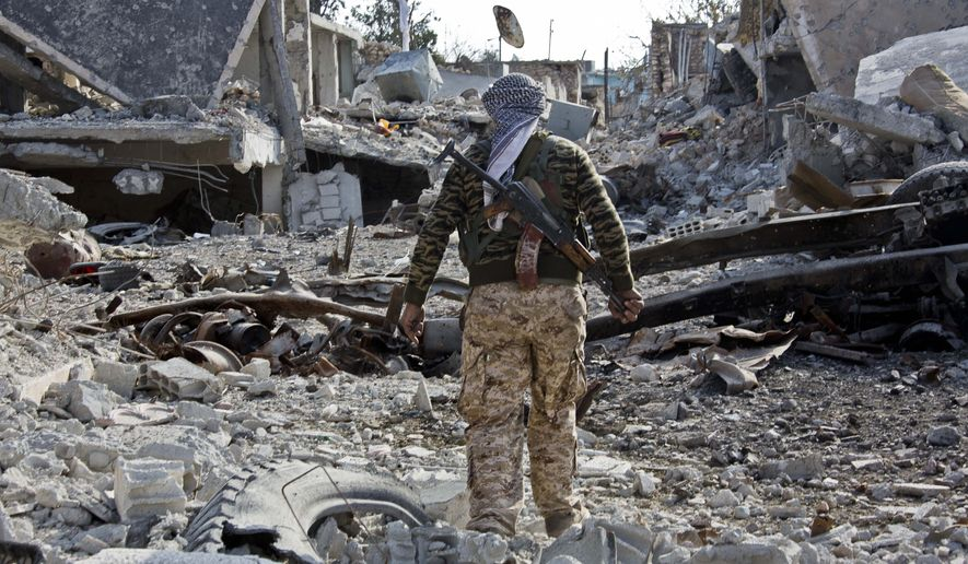 In this Wednesday, Nov. 19, 2014, photo, a Kurdish People's Protection Units (YPG) fighter shows the extent of the damage from a truck bomb in Kobani, Syria. (AP Photo/Jake Simkin)