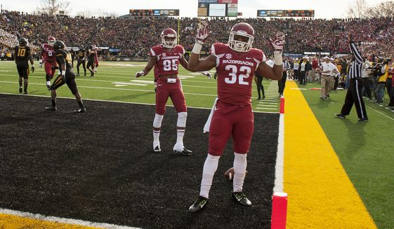Arkansas running back Jonathan Williams celebrates with teammate Demetrius Wilson (85) after Williams scored on a 23-yard reception during the first quarter of an NCAA college football game against Missouri, Friday, Nov. 28, 2014, in Columbia, Mo. (AP Photo/L.G. Patterson)