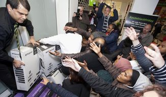 Shoppers jostle for electrical goods at a store in London, Friday Nov. 28, 2014. Americans celebrating Thanksgiving in Britain may have felt right at home as Black Friday shopping chaos caused some disruption. (AP Photo/PA, David Parry)