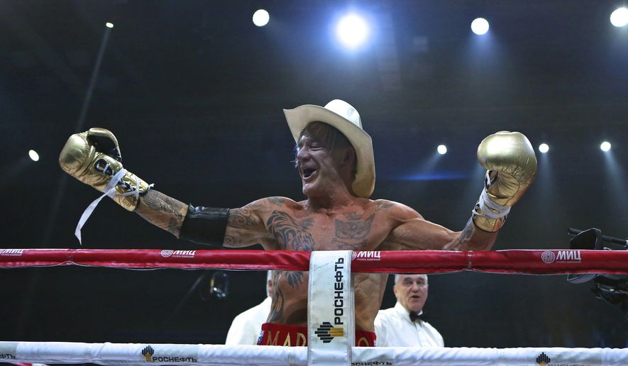 Actor Mickey Rourke celebrates his victory against his opponent Elliot Seymour of the United States, after their professional boxing match at the Luzhniki Stadium, Moscow, Friday, Nov. 28, 2014. Hollywood actor Mickey Rourke returned to the boxing ring Friday at the age of 62, defeating a fighter less than half his age in an exhibition bout. (AP Photo/Ivan Sekretarev)