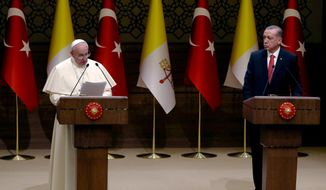 Turkish President Recep Tayyip Erdogan, right, listens to Pope Francis' speech at the Presidential palace in Ankara, Friday, Nov. 28, 2014. Pope Francis condemned the Islamic State assault on Christians and other religions minorities in Iraq and Syria as he arrived Friday in neighboring Turkey to encourage Muslim leaders to take a stronger stand against extremists who twist religion to justify terrorism. (AP Photo/Burhan Ozbilici)