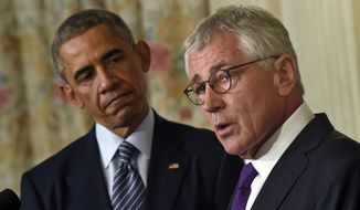 This  Nov. 24, 2014, file photo shows President Barack Obama, left, looking to Defense Secretary Chuck Hagel, right, as he talks about his resignation during an event in the State Dining Room of the White House in Washington. (AP Photo/Susan Walsh, File)