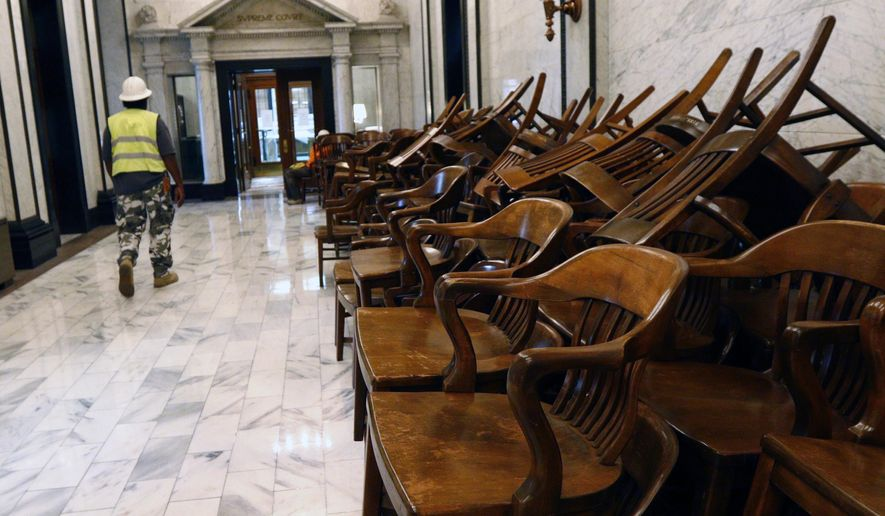 In this Nov. 21, 2014 photo, chairs from the Supreme Court chamber room on the Senate side of the Capitol in Jackson, Miss., are lined up along the hallway as a worker walked to the chamber during a repair and restoration project underway at the State Capitol that will address longtime water leaks, replace materials damaged by water and weather, and clean the exterior. The structure was built in 1903. (AP Photo/Rogelio V. Solis)