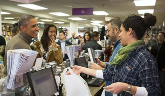 """President Barack Obama, left, joined by his daughter Malia, second from left, shops at Politics and Prose bookstore for """"Small Business Saturday,"""" on Saturday, Nov. 29, 2014, in Washington. (AP Photo/Evan Vucci)"""