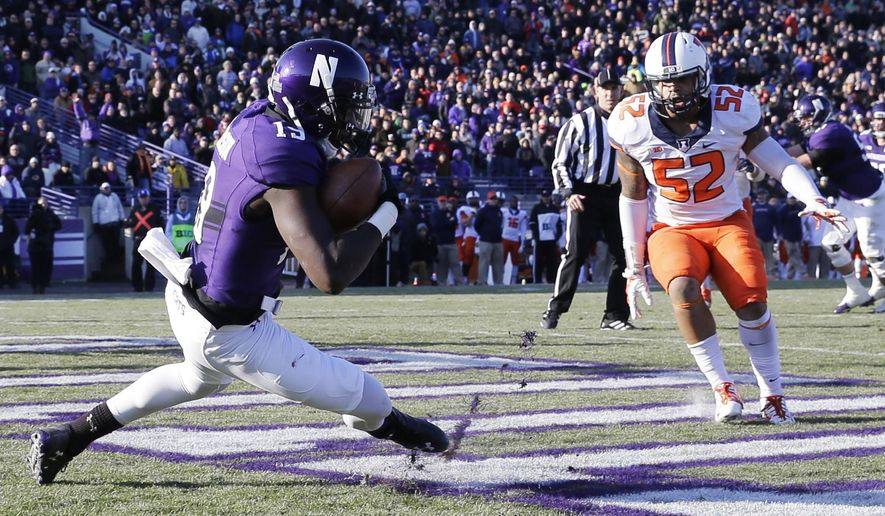 Northwestern wide receiver Cameron Dickerson (19) catches a touchdown pass as Illinois linebacker T.J. Neal Jr. (52) looks on during the second half of an NCAA college football game on Saturday, Nov. 29, 2014, in Evanston, Ill. Illinois won 47-33. (AP Photo/Nam Y. Huh)