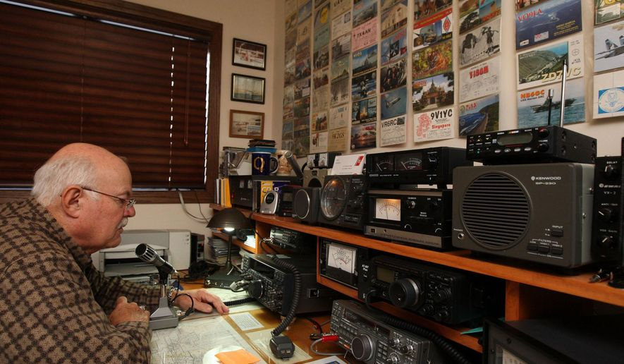 FOR RELEASE SATURDAY, NOVEMBER 29, 2014, AT 12:01 A.M. CST.- Sam Burrell makes a call on his ham radio in the room set up for his hobby Monday Nov. 17, 2014 at his home north of Burlington, Iowa. Burrell got hooked on the radio hobby in 1955 at the age of 14. The post cards on the wall are from some of the unique people his contacted including the International Space Station. (AP Photo/The Hawk Eye, John Gaines)