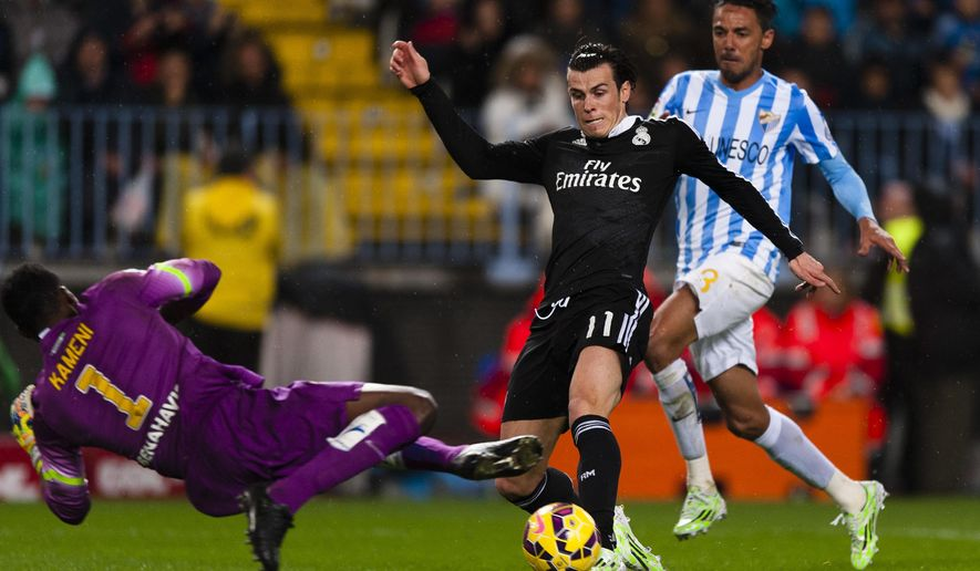 Real Madrid's Gareth Bale from Wales, center, duels for the ball against CF Malaga's goalkeeper Carlos Kameni from Cameroon, left, and Welligton Robson Pena de Oliveira from Brazil, right, during a Spanish La Liga soccer match between Malaga and Real Madrid at La Rosaleda stadium in Malaga, Spain, Saturday Nov. 29, 2014. (AP Photo/Daniel Tejedor)