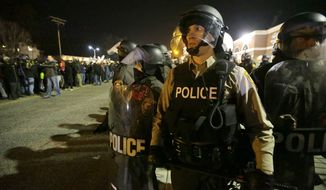 "FILE- In this Nov. 25, 2014 file photo, police watch the street as protesters gather in Ferguson, Mo. Missouri's governor ordered hundreds more state militia into Ferguson after a night of protests and rioting over a grand jury's decision not to indict police officer Darren Wilson in the fatal shooting of Michael Brown, a case that has inflamed racial tensions in the U.S. Departments around the country have in recent years stepped up their training in ""de-escalation"" — the art of defusing a tense situation with a word or a gesture instead of being confrontational or reaching for a weapon. (AP Photo/Charlie Riedel, File)"