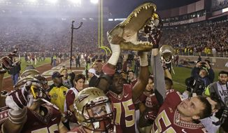 Florida State players celebrate in front of fans with a gator head after defeating rival Florida 24-19 in an NCAA college football game in Tallahassee, Fla., Saturday, Nov. 29, 2014. (AP Photo/John Raoux)