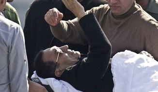 Former Egyptian President Hosni Mubarak, 86, greets medics, army personnel and his supporters, as he leaves a helicopter ambulance after it landed at Maadi Military Hospital following his verdict in Cairo, Egypt, Saturday, Nov. 29, 2014. An Egyptian court on Saturday dismissed criminal charges against former president Hosni Mubarak in connection with the killing of protesters in the 2011 uprising that ended his nearly three-decade reign. (AP Photo/Amr Nabil)