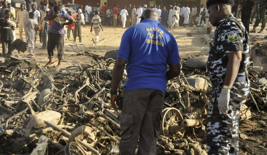 In this photo taken Friday, Nov. 28, 2014, Nigerian police inspect the site of an explosion in Kano, Nigeria. Multiple explosions tore through the central mosque in Nigeria's second-largest city on Friday, killing 35 people, police said. Hundreds gathered to listen to a sermon in the region terrorized by attacks from the militant group Boko Haram. (AP Photo/Muhammed Giginyu)