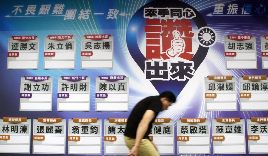 A staff of Taiwan's ruling Nationalist Party walks past a poster of candidate list with empty data at the headquarter in Taipei, Taiwan, Saturday, Nov. 29, 2014. In preliminary results, Taiwan's ruling Nationalist Party lost eight city and county elections Saturday, a stronger than expected jolt for the president who has staked his reputation on stronger ties with old foe Beijing despite increasing contempt at home. (AP Photo/Chiang Ying-ying)