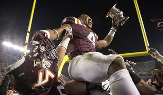Virginia Tech tailback J.C. Coleman (4) is lifted in air while holding the commonwealth cup after an NCAA college football game in Blacksburg, Va., Friday, Nov. 28, 2014. Virginia Tech won the game 24-20. (AP Photo/The Roanoke Times, Shaban Athuman)  LOCAL TELEVISION OUT; SALEM TIMES REGISTER OUT; FINCASTLE HERALD OUT;  CHRISTIANBURG NEWS MESSENGER OUT; RADFORD NEWS JOURNAL OUT; ROANOKE STAR SENTINEL OUT