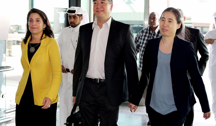 American couple Grace, right, and Matthew Huang walk to their departure gate with U.S. Ambassador to Qatar, Dana Shell Smith, left, at the Hamad International Airport in Doha, Qatar, Sunday, Nov. 30, 2014. A Qatari appeals court on Sunday overturned a ruling against an American couple over the death of their adopted daughter and said they are free to leave, ending a closely watched legal saga that may have stemmed from cultural misunderstandings in the conservative Gulf nation. (AP Photo/Osama Faisal)