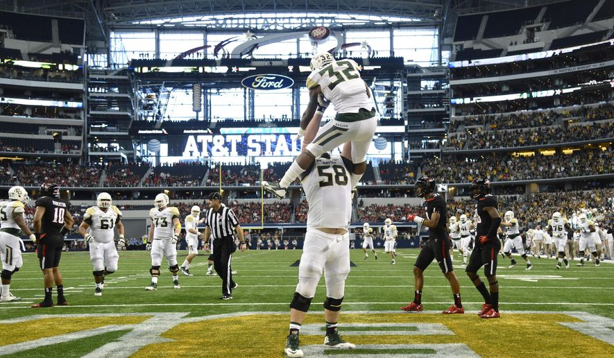 Baylor running back Shock Linwood (32) celebrates with offensive tackle Spencer Drango (58) after scoring a touchdown in the first half of an NCAA college football game against the Texas Tech, Saturday, Nov. 29, 2014, in Arlington, Texas. Baylor won 48-46. (AP Photo/Tim Sharp)