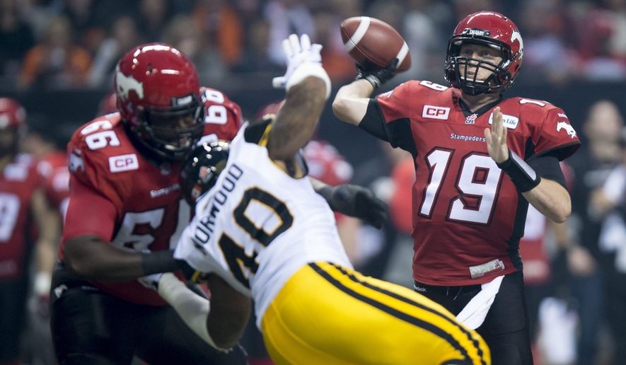 Calgary Stampeders quarterback Bo Levi Mitchell (19) throws the ball a Stampeders offensive lineman Stanley Bryant holds off Hamilton Tiger-Cats defensive end Eric Norwood during the first half of the CFL Grey Cup in Vancouver, British Columbia, Sunday, Nov. 30, 2014. (AP Photo/The Canadian Press, Paul Chiasson)
